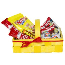 Шоколадные батончики в ярких упаковках в желтой подарочной корзине.