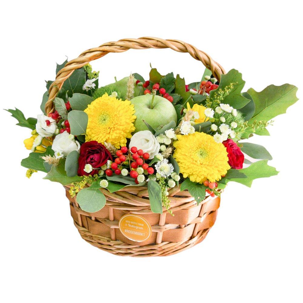 Зелёные яблоки с яркими цветами в плетеной корзинке