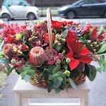 Буплерум, гвоздика красная, гиперикум красный, орхидея Цимбидиум розовая, пионы бордовые, пуансеттия красная, роза кустовая красная, скиммия красная, цветы на выбор флориста, эвкалипт