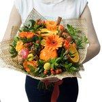 Букет из апельсинов, оранжевых гербер, красного гиперикума, корицы, краспедии, кустовых оранжевых роз, фисташки, красных яблок в Санкт-Петербурге