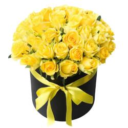 Букет в черной шляпной коробке, подчеркивающей яркость желтых роз