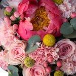 Нежно-розовый букет с яркими акцентами  — коралловым пионом и краспедией в стильной чёрной упаковке в Санкт-Петербурге