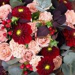 Букет из бордовых георгин, роз Капучино, персиковых гвоздик и ягодок гиперикума в Санкт-Петербурге