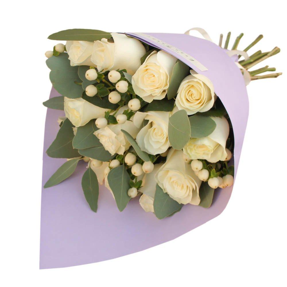 Букет из белых роз с ягодками гиперикума и эвкалиптом в стильной упаковке в Санкт-Петербурге